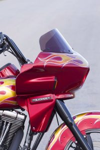 photo of a custom red harley davidson dyna switchback FLD with a wedge fairing viewed from the side